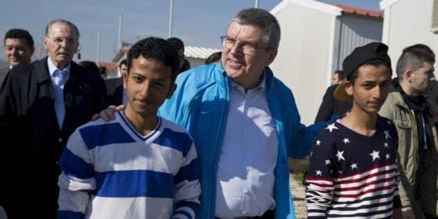 IOC President Thomas Bach, center, walks with two young refugees with former IOC President Jacques Rogge in the background, during their visit at a refugee camp in Athens on Thursday, Jan, 28, 2016. Bach says the torch relay for this year's Olympics in Rio de Janeiro will include a stop at a refugee camp in Athens. He also promised to build sporting facilities on the island of Lesbos that has been hard hit by the migrant crisis.(AP Photo/Petros Giannakouris)