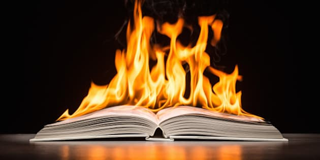 Open hard covered book engulfed in flame