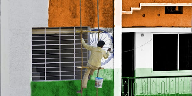 Man coloring pattern of national flag of India on the wall of a building hanging in a rope ladder