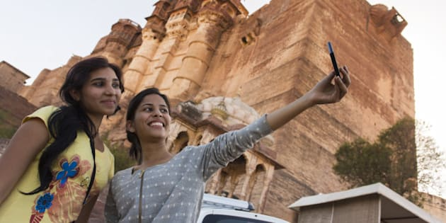 Two girls taking a tourist self portrait or selfie photo on a mobile phone at the Amber Fort.