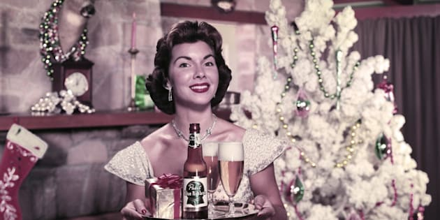 Portrait of an unidentified model as she stands in front of a Christmas tree next to a fireplace with a bottle of Pabst Blue Ribbon beer, two glasses, and a present on a serving tray, 1951. (Photo by Tom Kelley/Getty Images)