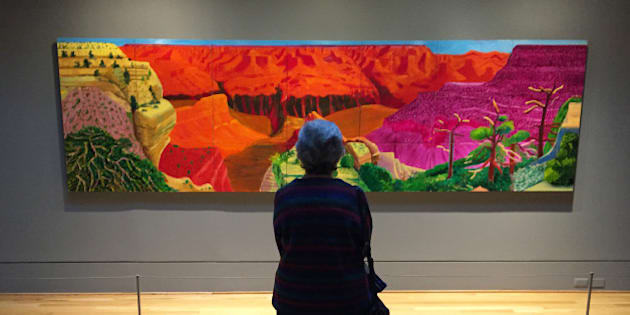 """This Feb. 20, 2016 photo shows a visitor gazing at David Hockney's depiction of the Grand Canyon in a show called """"Seeing Nature"""" at the Phillips Collection in Washington, D.C. The Phillips, a modern art museum, is one of the top attractions in the Dupont Circle neighborhood. (AP Photo/Beth J. Harpaz)"""