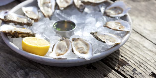 fresh raw oysters served with lemon and sauce at the plate with ice