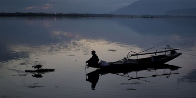 A Kashmiri fisherman prepares to bring to shore his Shikara, or traditional boat, after a days work at the Dal Lake on the outskirts of Srinagar, Indian controlled Kashmir, Wednesday, April 8, 2015. Nestled in the Himalayan mountains and known for its beautiful lakes and saucer-shaped valleys, the Indian portion of Kashmir, is also one of the most militarized places on earth.(AP Photo/Dar Yasin)