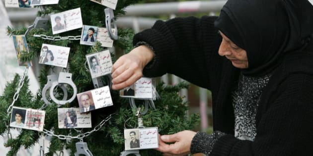 Lebanese Hana Yehya, mother of Mustafa Zakzouk who was detained in 1988 and believed to be still held in a prison in Syria, decorates a Christmas tree with handcuffs and photos of missing persons, in Beirut, Lebanon, Thursday, Dec. 22, 2005. Seventeen thousand people are still missing since the end of the 1975-90 Lebanese civil war. (AP Photo/Hussein Malla)