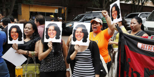 People hold up photos of slain Honduran indigenous leader and environmentalist Berta Caceres outside the coroners office in Tegucigalpa, Honduras, Thursday, March 3, 2016. Caceres, a Lenca indigenous activist who won the 2015 Goldman Environmental Prize for her role in fighting a dam project, had previously complained of receiving death threats from police, soldiers and local landowners because of her work. (AP Photo/Fernando Antonio)