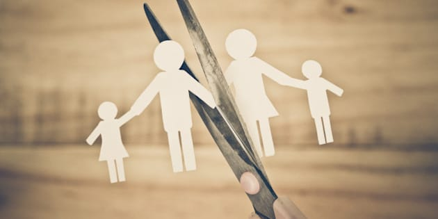 Hand with scissors cutting paper cut out with family member shape / Family problem / Divorce concept