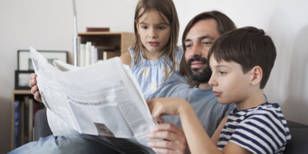 Father and children reading newspaper on sofa at home