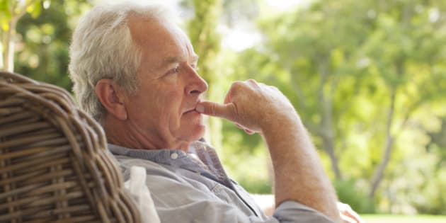 Pensive senior man sitting in wicker armchair on porch