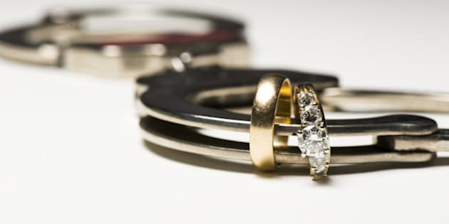 a close up of wedding rings and a handcuff showing people locked in love.