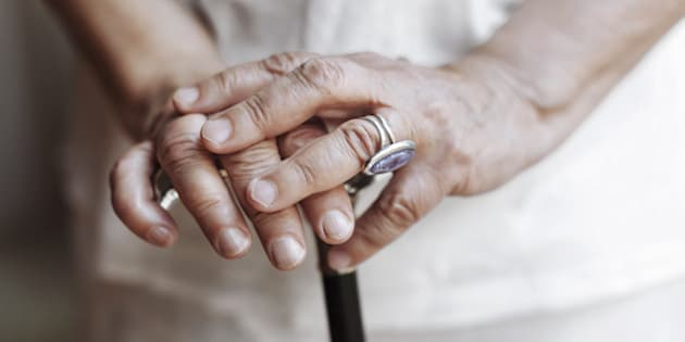 Close-up shot of senior woman's hands holding a crutch.