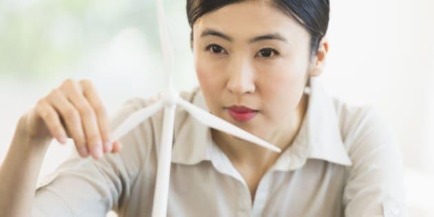 Female engineer working on model of wind turbine