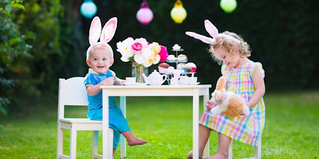 Little boy and girl play toy tea party outdoors. Children with bunny ears on Easter egg hunt. Kids playing in the garden in spring. Toddler and baby with toy rabbit and doll dishes. Family celebration