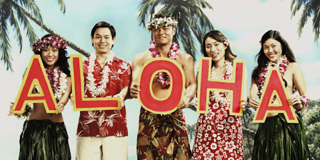 Tourists and native dancers holding letters spelling 'Aloha'