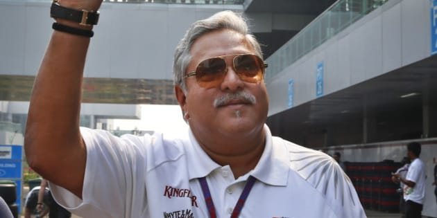 Force India team principal and businessman Vijay Mallya waves as he walks down the F1 paddock after the third practice session for the Indian Formula One Grand Prix at the Buddh International Circuit in Noida, on the outskirts of New Delhi, India, Saturday, Oct. 27, 2012. (AP Photo/Saurabh Das)