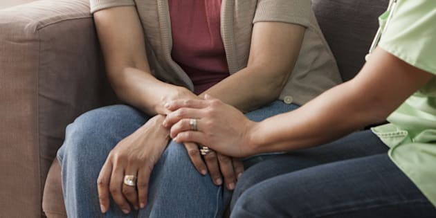 Mother and daughter holding hands on sofa