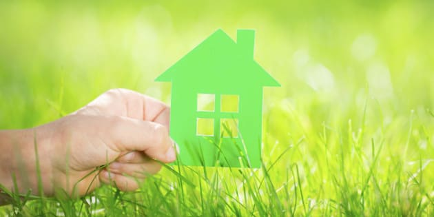 Paper house in children`s hand against green spring background. Real estate concept