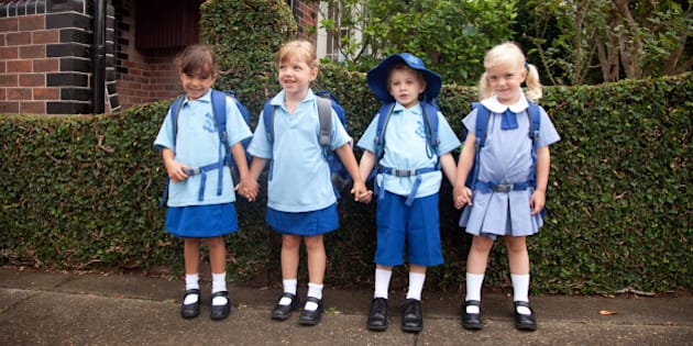 1 dark hair girl 5yr and 1 blonde boy 5yrs holding hands all in school uniform in front of a hedge