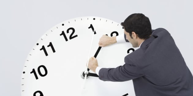Businessman pushing back hands of clock