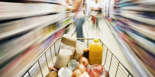 Shopping cart approaches woman in aisle. Motion blur.