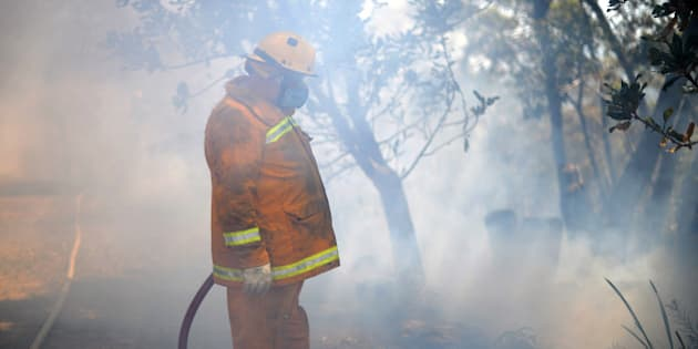 A firefighter is pictured working on a back burn operation to clear brush as bush fires approach near Faulconbridge in the Blue Mountains on October 24, 2013. Thousands of largely volunteer firefighters have been battling infernos for more than a week across the state of New South Wales that have destroyed over 200 homes, with the Blue Mountains region west of Sydney the focal point.   AFP PHOTO / Saeed KHAN        (Photo credit should read SAEED KHAN/AFP/Getty Images)