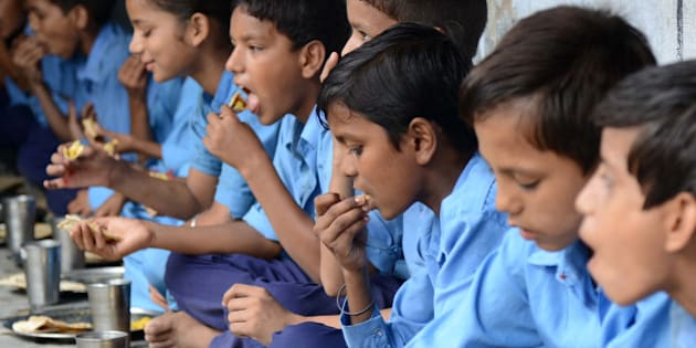 Indian schoolchildren eat their free mid-day meal at a government school in Amritsar on July 19, 2013. Punjab state Education Minister Sikander Singh Maluka issued directions to all authorities concerned to observe hygiene regulations in serving the mid-day meal and said all principals and heads of schools would be held personally accountable for any discrepancies in the service. Twenty-three children died on July 17, after eating a free lunch feared to contain poisonous chemicals at a school in thee eastern Indian state of Bihar.   AFP PHOTO/NARINDER NANU        (Photo credit should read NARINDER NANU/AFP/Getty Images)