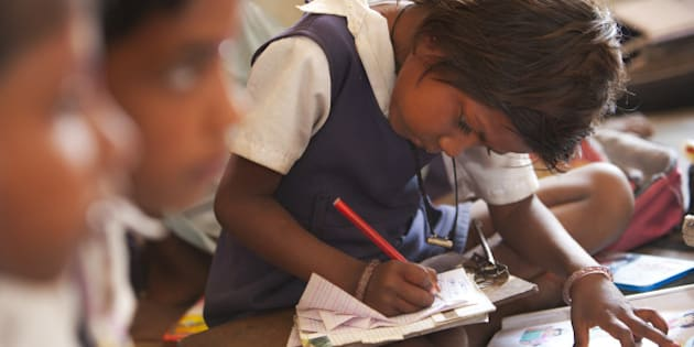Indian schoolgirl studying in the classroom at her poor village school outside Bandhavgarh National Park. The children sit barefoot on the floor to learn their lessons. She is wearing a school uniform.