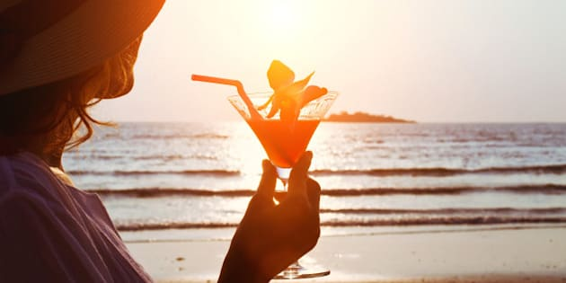 silhouette of woman with cocktail on the beach