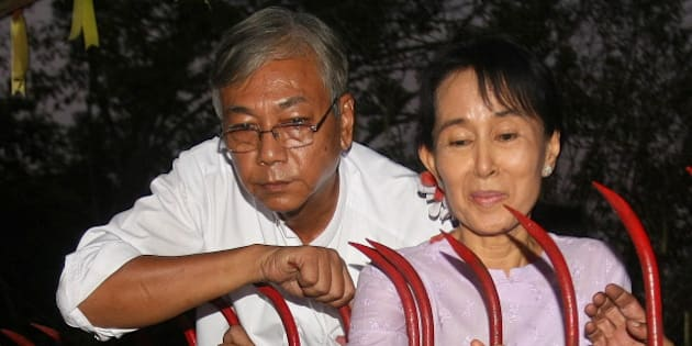 Myanmar's opposition leader Aung San Suu Kyi (R) appears with Htin Kyaw (L) a senior National League for Democracy (NLD) official, at the gate  of her house in front of cheering supporters after her release in Yangon on November 13, 2010.  Myanmar's democracy leader Aung San Suu Kyi walked free from the lakeside home that has been her prison for most of the past two decades, to the delight of huge crowds of waiting supporters. Waving and smiling, the petite but indomitable Nobel Peace Prize winner appeared outside the crumbling mansion where she had been locked up by the military junta for 15 of the past 21 years.     AFP PHOTO/Soe Than WIN / AFP / Soe Than WIN        (Photo credit should read SOE THAN WIN/AFP/Getty Images)
