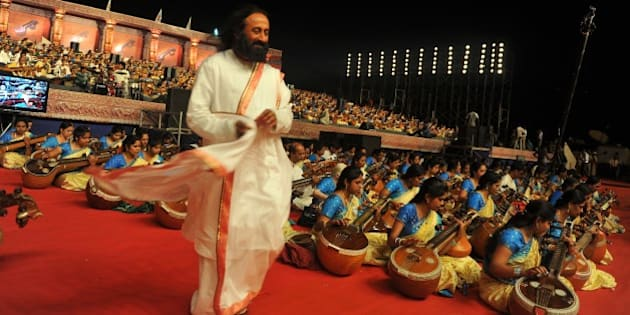 Spiritual leader and founder of Art of Living foundation Sri Sri Ravishankar (C), walks among Indian musicians participating in the 'Shasra Veena Jhenkara' (thousand veena recital), a concert featuring 1110 artists rendering 'Veena' the Indian classical music instrument in Bangalore on March 28, 2012. AFP PHOTO/Manjunath KIRAN (Photo credit should read Manjunath Kiran/AFP/Getty Images)