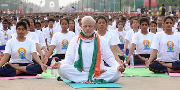 NEW, DELHI - INDIA: Indian Prime Minister Narendra Modi (C) performs yoga along with others at Rajpath during mass yoga session to mark the International Day of Yoga on June 21, 2015 in New Delhi, India. An estimated 40,000 people participated in the celebrations at Rajpath, with around two billion people taking part across the world. The yoga celebrations are being organised after the United Nations had in December last year declared June 21 as International Yoga Day. (Photo by Vinod Singh/Anadolu Agency/Getty Images)