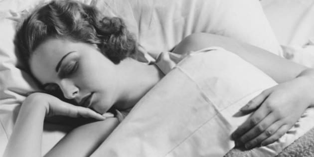 Young woman asleep in bed, (B&W), close-up