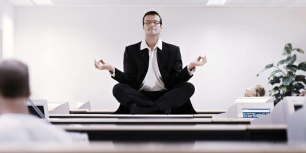 Businessman meditating on office desk