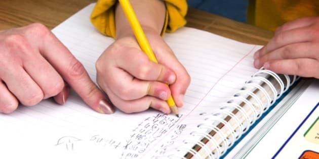 Mother or teacher helping boy with homework