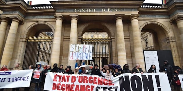 People holding a banner reading 'state of emergency, deprivation of citizenship, no!' take part in a demonstration on January 30, 2016 outside the Council of State in Paris, to protest against government plans to extend a state of emergency for another three months after the November terror attacks in Paris as well as plans to enshrine some of these measures in the constitution. / AFP / ALAIN JOCARD        (Photo credit should read ALAIN JOCARD/AFP/Getty Images)