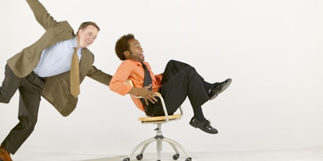 Businessmen goofing off with office chair