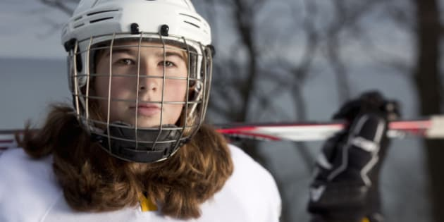 Eleven year old girl hockey player portrait on an ice rink overlooking Lake Michigan in Wisconsin.