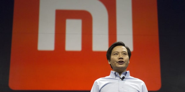 Xiaomi Chairman Lei Jun stands in front of the logo of the Chinese smartphone maker, at a press event in Beijing, Thursday, Jan. 15, 2015. The Chinese manufacturer on Thursday unveiled a new model that Lei said has processor size and performance comparable to Apple's iPhone 6 but is thinner and lighter. (AP Photo/Ng Han Guan)