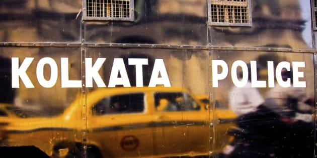 Yellow Ambassador taxi reflecting in black van with Kolkata police inscription. Calcutta, India.