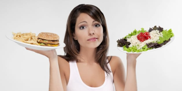 Woman choosing between a hamburger and salad