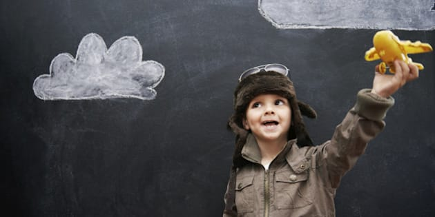 A little boy playing with a yellow toy airplane in front of clouds drawn on a blackboard