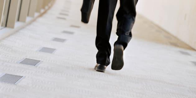 Businessman on mobile phone walking down a corridor