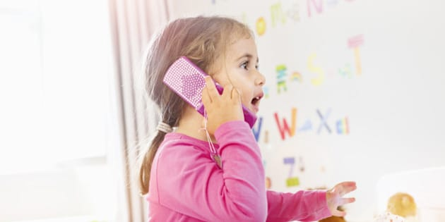young girl is talking on toy mobile phone.