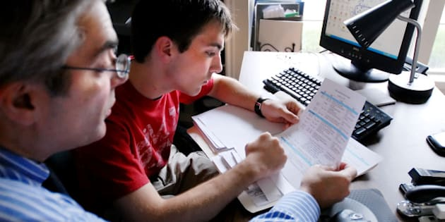 Chris Economou, left, a financial planner, goes over college paperwork with son Thane 18, in their home office in Tulsa, Okla. Saturday Sept. 2, 2006. Financial planners face the same issues that other parents do when their kids head off to college: Should they take checks, debit cards, credit cards _ or some combination of the three? The experts seem to favor checks and debit cards for day-to-day spending with a credit card tucked away somewhere safe for emergencies. (AP Photo/Brandi Simons)