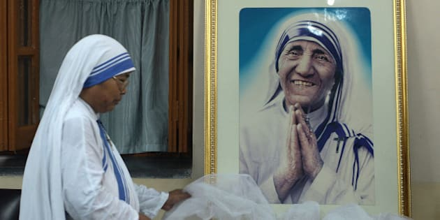 TOPSHOT - A nun of ?the Missionaries of Charity decorates a picture of Mother Teresa prior to a special prayer service at Mother House in Kolkata on December 18, 2015.   Mother Teresa, set to become a saint after the Vatican announced recognition of her second miracle, became a global symbol of compassion for her care of the sick and destitute. / AFP / DIBYANGSHU SARKAR        (Photo credit should read DIBYANGSHU SARKAR/AFP/Getty Images)