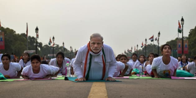 Indian Prime Minister Narendra Modi lies down on a mat as he performs yoga along with thousands of Indians on Rajpath, in New Delhi, India, Sunday, June 21, 2015. Millions of yoga enthusiasts are bending their bodies in complex postures across India as they take part in a mass yoga program to mark the first International Yoga Day.(AP Photo/Saurabh Das)