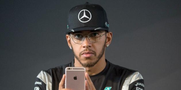 Lewis Hamilton, piloto de la Fórmula Uno, observa su iPhone durante una conferencia de prensa en Fellbach, Alemania, el viernes 11 de marzo de 2016 (Marijan Murat/dpa via AP)