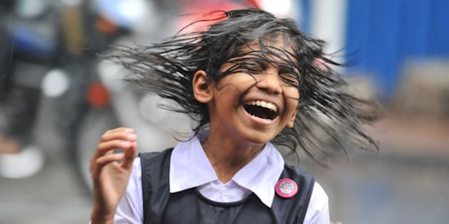 An Indian child shakes her hair during a heavy downpour of rain as she waits for transport outside her school in Hyderabad on August 19, 2011.   Monsoon rains are a key factor for global commodities markets,  strengthening the output of various crops in India, which could help bring relief to Asia's third-largest economy in its battle with high food prices. AFP PHOTO/Noah SEELAM (Photo credit should read NOAH SEELAM/AFP/Getty Images)