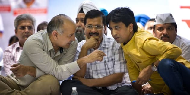 Delhi Chief Minister Arvind Kejriwal sits flanked by Aam Aadmi Party or Common man's party leaders Manish Sisodia, left and Kumar Vishwas at a farmer's rally near the Indian parliament in New Delhi, India, Wednesday, April 22, 2015. Indian farmers and the opposition parties are protesting against a government plan to ease rules for obtaining land for industry and development projects. (AP Photo/Saurabh Das)