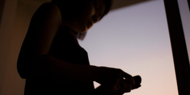 Playing with her smartphone at the window during sunset.